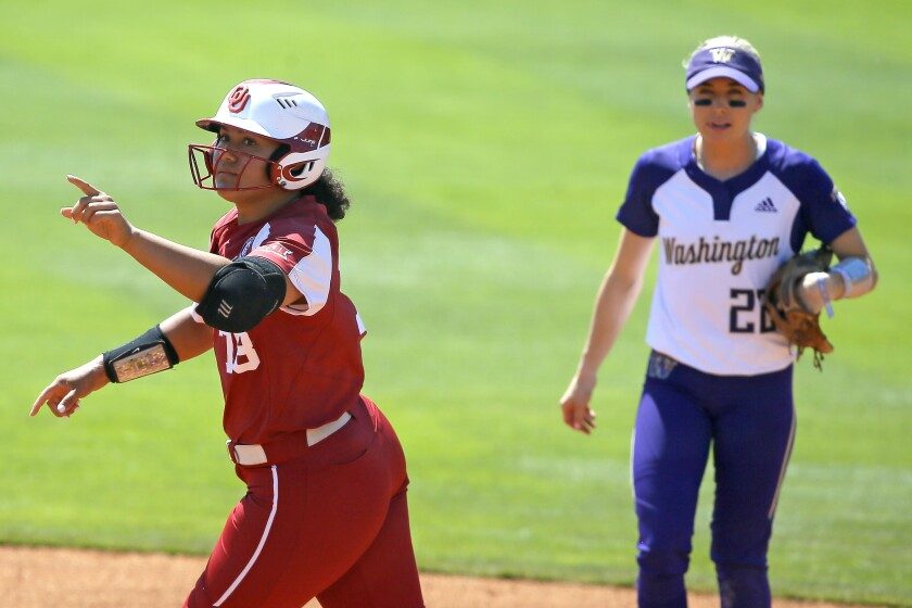 Oklahoma's Jocelyn Alo (78) gestures as she runs past Washington's Sis Bates (22) after hitting a home run in the fourth inning of the second game in an NCAA college softball tournament super regional in Norman, Okla., Saturday, May 29, 2021. (Bryan Terry/The Oklahoman via AP)