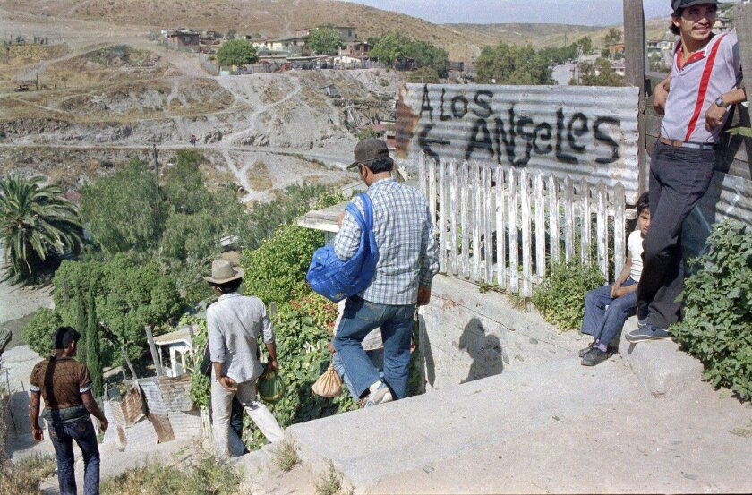 In April 1985, migrants passed a metal sign at the U.S.-Mexico border pointing the way to Los Angeles.