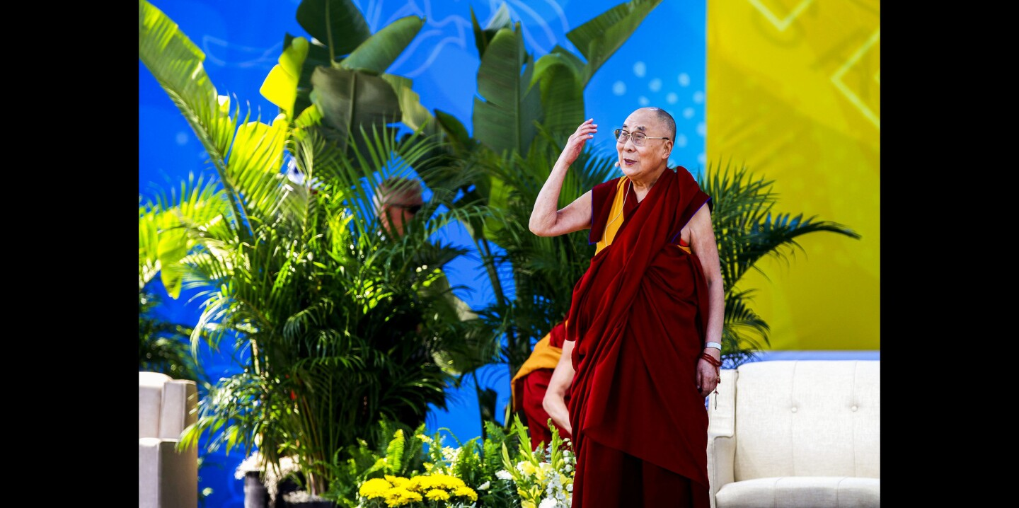 """The Dalai Lama waves after he walked on stage for his public address, titled """"Embracing the Beauty of Diversity in our World""""."""