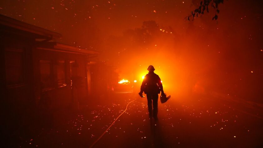 A firefighter walks towards his engine after trying to prevent the Woolsey fire from overtaking structures in Malibu Friday. No public schools in Ventura County were directly hit, but a Jewish school suffered significant damage.