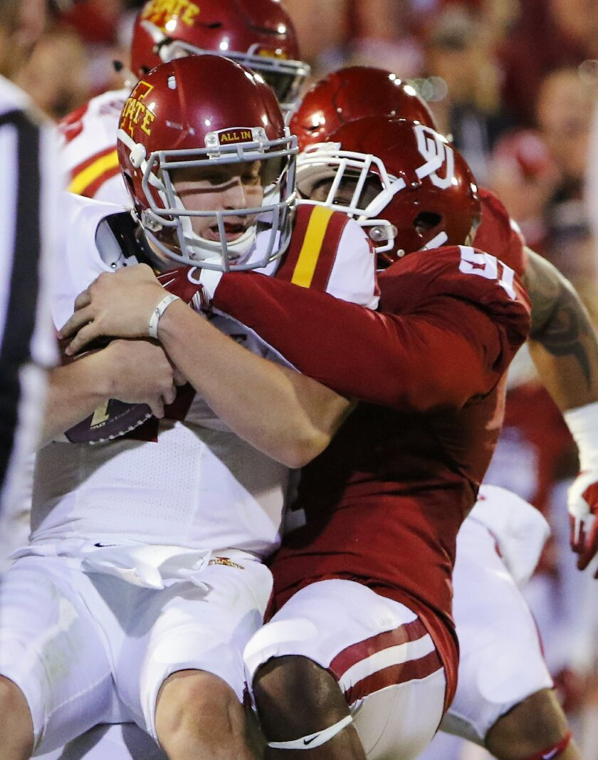 Iowa State quarterback Joel Lanning is sacked by Oklahoma defensive end Charles Tapper (91) during the first quarter of an NCAA college football game in Norman, Okla., on Saturday, Nov. 7, 2015. (AP Photo/Alonzo Adams)