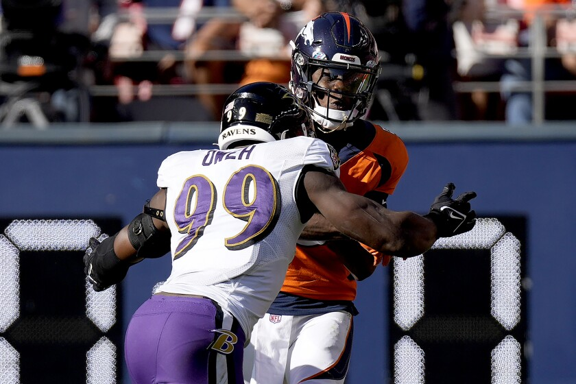 Denver Broncos quarterback Teddy Bridgewater is hit by Baltimore Ravens linebacker Odafe Oweh (99) during the first half of an NFL football game, Sunday, Oct. 3, 2021, in Denver. (AP Photo/David Zalubowski)