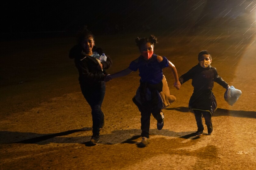 FILE - In this May 11, 2021 file photo three young migrants hold hands as they run in the rain at an intake area after turning themselves in upon crossing the U.S.-Mexico border in Roma, Texas. An official says the Biden administration has begun flying some Central American families deep into Mexico as authorities encounter more families and unaccompanied children at the U.S.-Mexico border. (AP Photo/Gregory Bull, File)