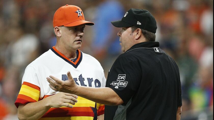 Manager A.J. Hinch of the Houston Astros talks with umpire Doug Eddings after Alex Bregman claimed he fouled the ball off his foot against the Mariners.