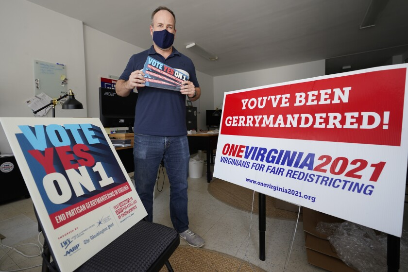 FILE - In this Oct. 6, 2020, file photo, redistricting reform advocate Brian Cannon poses with some of his yard signs and bumper stickers in his office in Richmond, Va. Negotiations broke down Friday, Oct. 8, 2021, between members of Virginia's bipartisan redistricting commission after Democrats and Republicans failed to agree on which proposed maps they should use as a starting point. (AP Photo/Steve Helber, File)