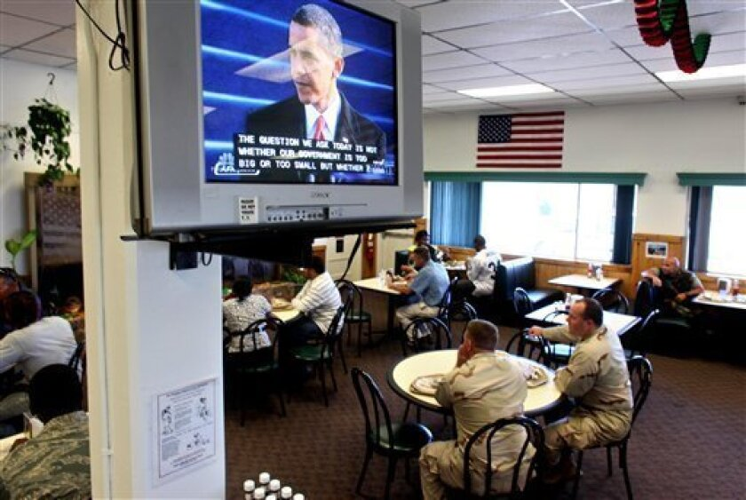 U.S. military personnel inside a cafeteria watch live as President Barack Obama delivers his inaugural address after being sworn in as the 44th President of the United States, at the U.S. Naval Base, in Guantanamo Bay, Cuba, Tuesday, Jan. 20, 2009. (AP Photo/Brennan Linsley, Pool)