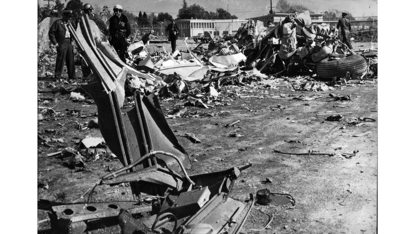 Jan. 31, 1957: Military and police personnel at scene of crash of Douglas DC-7B transport on grounds