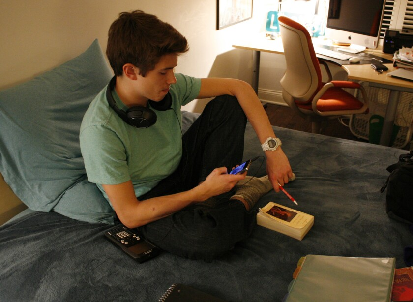 Multitasking is the new norm among teens and tweens, according to a report from Common Sense Media. Donald Conkey, 15, checks his smartphone while doing homework in his bedroom in Wilmette, Ill.