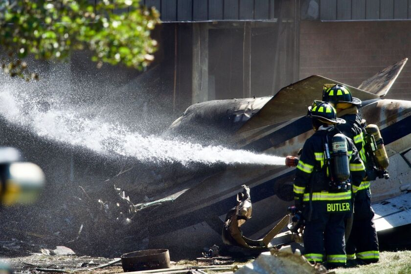 Firefighters spray water at the scene of a plane crash, in Farmington, Conn., Thursday. Sept. 2, 2021. All four people aboard a small jet were killed Thursday morning when it crashed shortly after taking off from Robertson Airport before crashing into the building at Trumpf Inc., a manufacturing company, Farmington Police Lt. Tim McKenzie said. (Mark Mirko/Hartford Courant via AP)