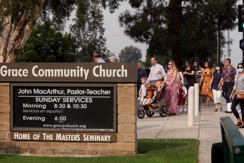 People, only a few wearing masks, walk past a sign into the entrance of Grace Community Church