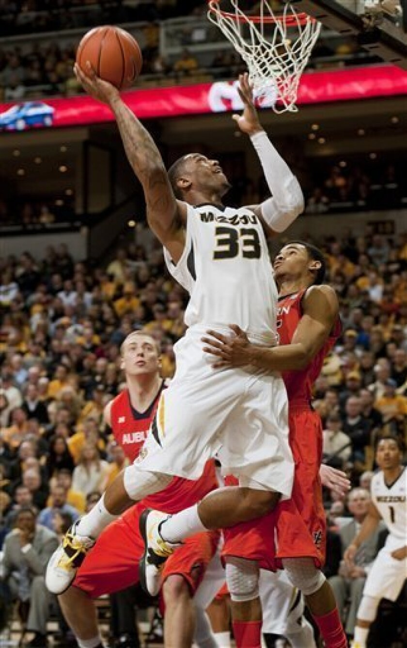 Missouri's Earnest Ross, top, shoots over Auburn's Shaquille Johnson, right, and past Rob Chubb, left, during the first half of an NCAA college basketball game Saturday, Feb. 2, 2013, in Columbia, Mo. (AP Photo/L.G. Patterson)