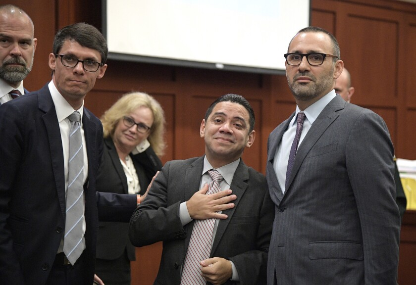 Clemente Aguirre (c.) reacts in the courtroom with his attorneys after he was exonerated of all charges in the 2004 murders of Carol Bareis and Cheryl Williams on Monday in Sanford, Fla.