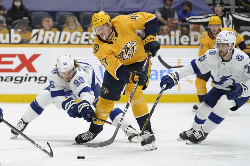 Tampa Bay Lightning defenseman Mikhail Sergachev (98) battles for the puck with Nashville Predators right wing Michael McCarron (47) in the first period of an NHL hockey game Saturday, April 10, 2021, in Nashville, Tenn. (AP Photo/Mark Humphrey)
