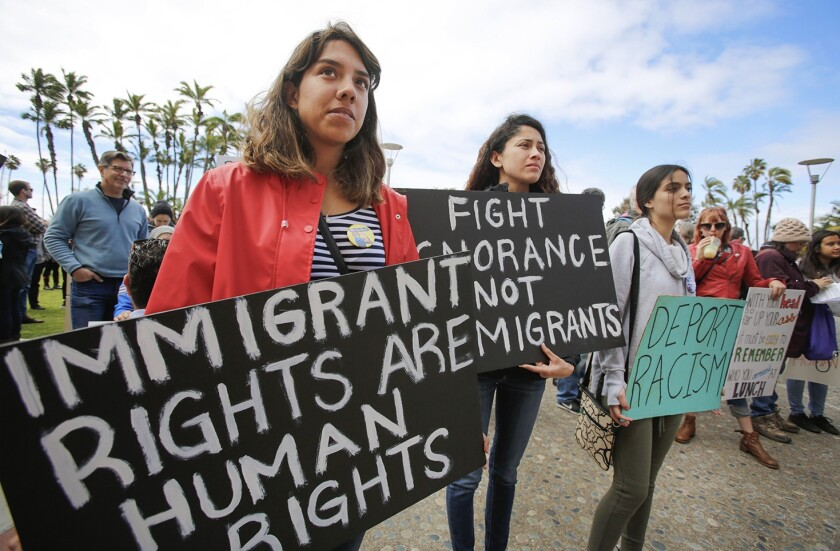 """Women hold signs reading: """"Immigrant rights are human rights,"""" """"Fight ignorance not immigrants,"""" and """"Deport racism."""""""