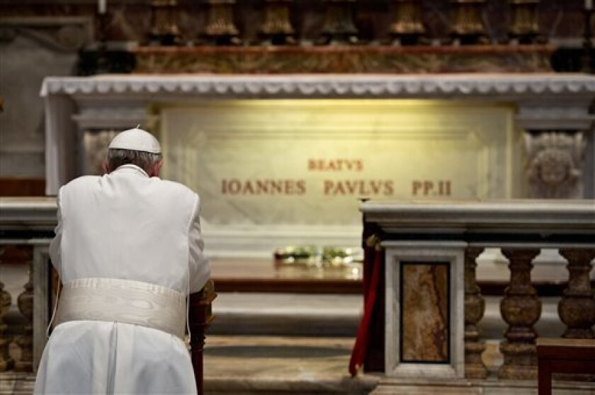 In this picture made available by the Vatican newspaper L'Osservatore Romano, Pope Francis prays in front of the tomb of Pope John Paul II, at the Vatican Tuesday, April 2, 2013. Pope Francis has prayed before the tomb of Pope John Paul II on the eighth anniversary of the much-beloved pontiff's death. In his three weeks as pope, Francis has jolted the Catholic Church with several gestures that broke with tradition, including renouncing certain liturgical vestments and washing the feet of a Musli