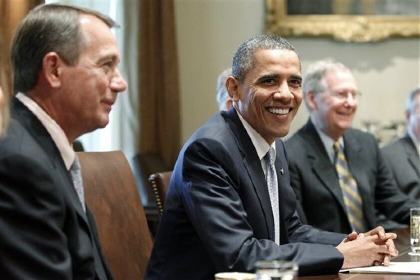 President Barack Obama smiles as he sits with House Speaker John Boehner of Ohio, left, and Senate Minority Leader Mitch McConnell of Ky., in the Cabinet Room of the White House in Washington, Wednesday, July 13, 2011, as he met with Congressional leaders regarding the debt ceiling. (AP Photo/Charles Dharapak)