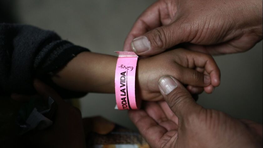 A child wears a bracelet marked with a number that indicates his place in line to submit his request