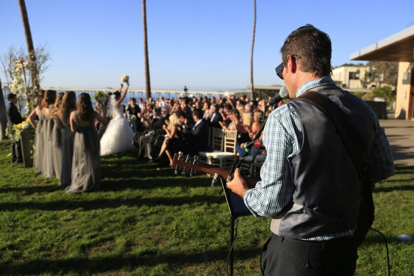 Wedding singer Michael Tiernan plays guitar as a newlywed couple walks down the aisle to the applause of family and friends.