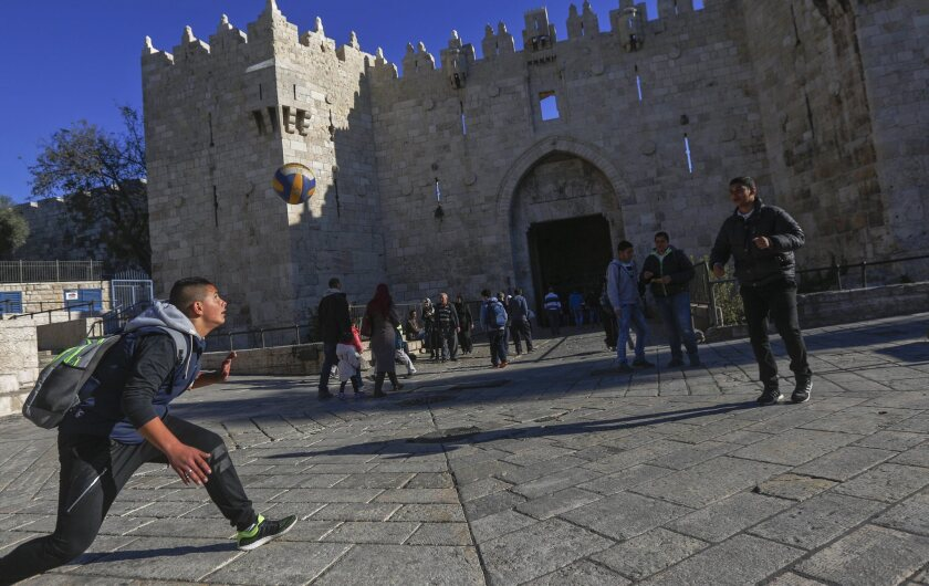 Palestinian students play with a ball in front of the landmark Damascus Gate in the Old City of Jerusalem on Dec. 9, 2015.