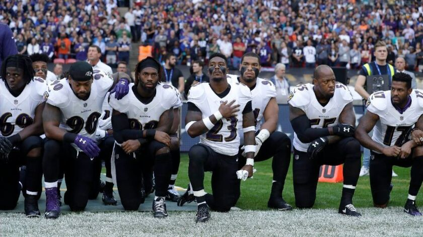 Members of the Baltimore Ravens kneel in protest during the playing of the national anthem before a