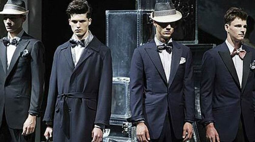 """ALFRED DUNHILL: Dark blue suits and coats with shimmering elements add to the """"faded futurism"""" theme."""