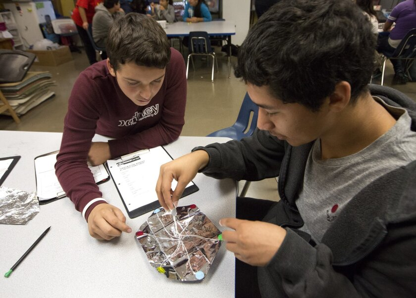 Marcos Salazar (left) and Jose Tapia, consult on their parachute design during an experiment at the Reuben H. Fleet Science Center.