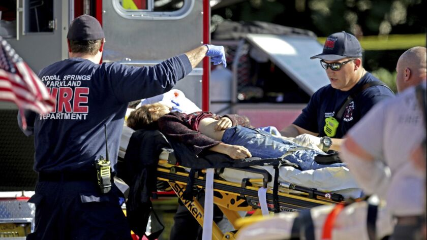 Medical personnel tend to a victim following a shooting at Marjory Stoneman Douglas High School in P
