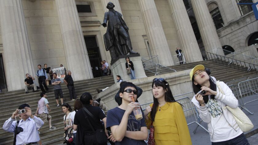 FILE - In this Friday, June 15, 2012, file photo, a group of tourists from China take in the sights