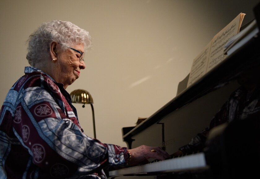Joanne Rogers plays the piano in her Pittsburgh apartment.