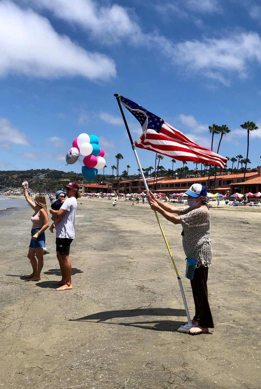 Friends and family members of La Jollan Laura McDonald await her at La Jolla Shores after she completed a 4-mile swim.