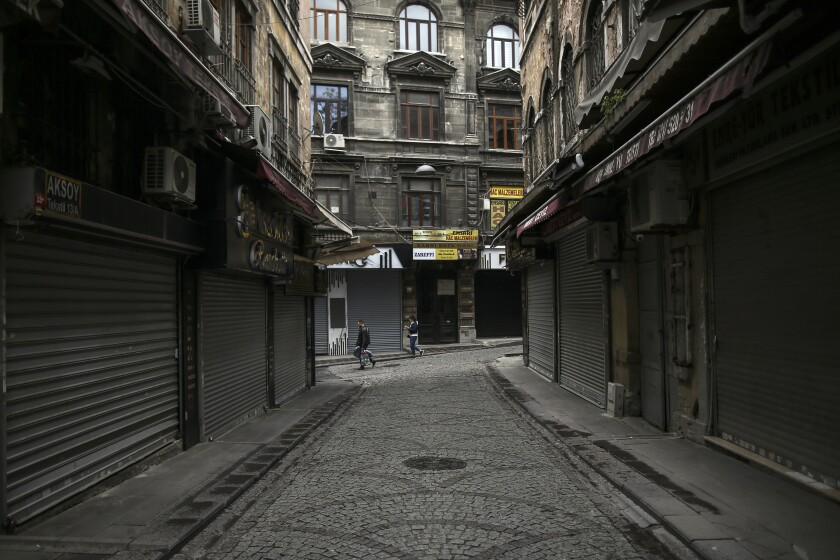 Dos personas caminan por las calles del mercado de Eminonu, en Estambul, una zona usualmente atestada pero ahora casi desierta debido al estricto confinamiento por la pandemia de coronavirus, el sábado 8 de mayo de 2021. (AP Foto/Emrah Gurel)
