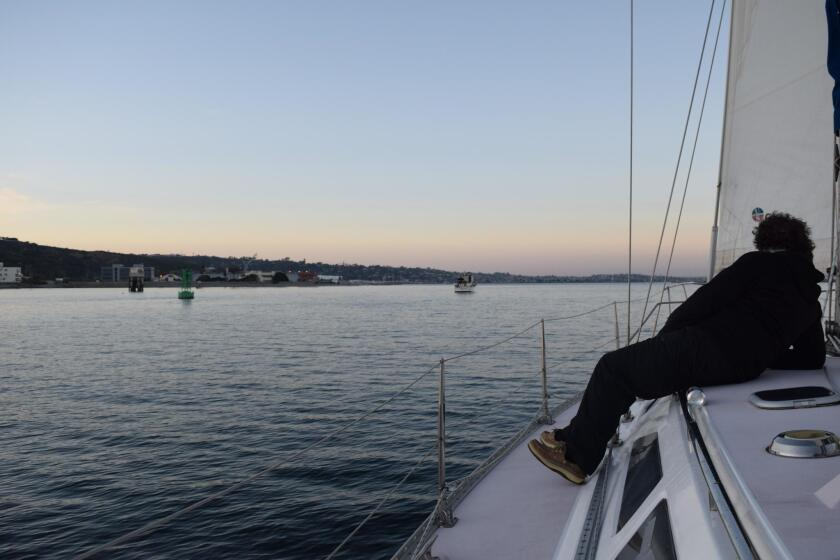 Passenger Stephen Gallogly reclines on the boat to savor the scenery.