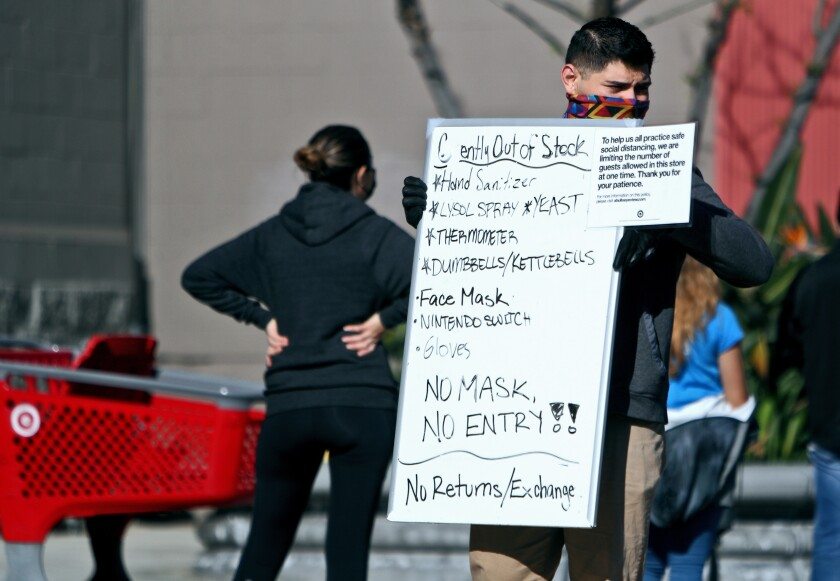A Target employee walks along the customer line with a sign saying customers have to wear a mask to enter the Burbank store.