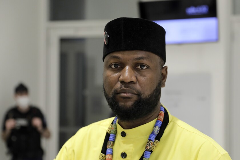 Congo-born Emery Mwazulu Diyabanza looks on after the verdict at the Paris Palace of Justice, Wednesday, Oct. 14, 2020. Diyabanza was fined 2,000 euros ($2,320) for trying to take a 19th-century African funeral pole from a Paris museum. He streamed the incident online in a protest against colonial-era injustice like the plundering of African art. (AP Photo/Lewis Joly)