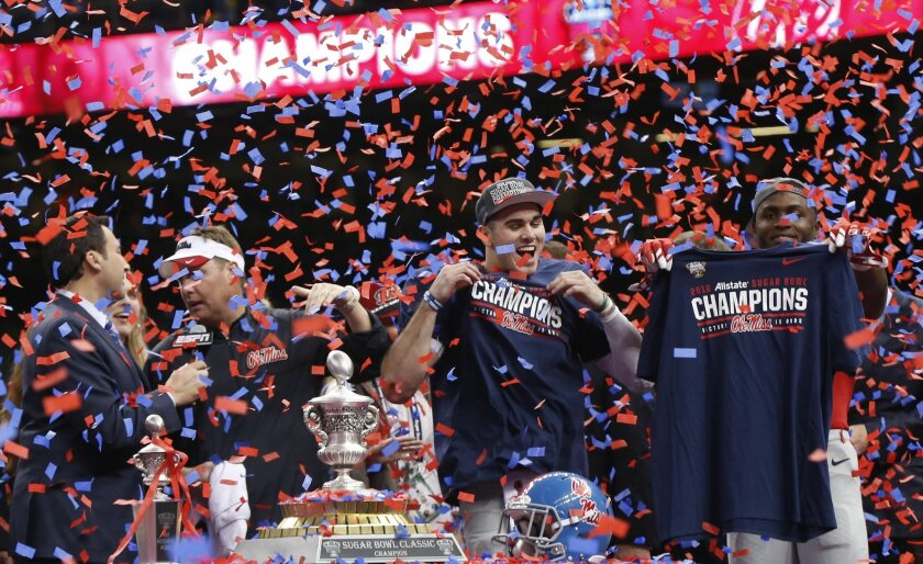 Mississippi wide receiver Laquon Treadwell, left, quarterback Chad Kelly, second left, and head coach Hugh Freeze, third left, celebrate as confetti rains down after the Sugar Bowl college football game against Oklahoma State in New Orleans, Friday, Jan. 1, 2016. Mississippi won 48-20. (AP Photo/Bill Feig)