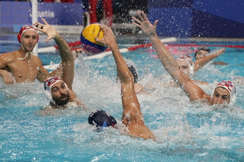 Croatia's Marko Macan (2) and Maro Jokovic (5) defend against Serbia's Strahinja Rasovic (7) during a preliminary round men's water polo match at the 2020 Summer Olympics, Saturday, July 31, 2021, in Tokyo, Japan. (AP Photo/Mark Humphrey)