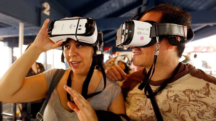Jenny Alvarez, left, and Alfonso De Elias prepare to ride the New Revolution Virtual Reality roller coaster at Six Flags Magic Mountain in Valencia last year. (Al Seib / Los Angeles Times)