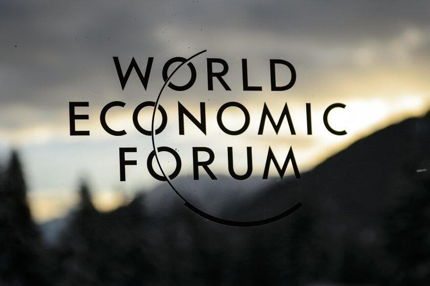 The World Economic Forum logo is pictured through a window on the eve of the opening of the Annual Meeting of the World Economic Forum, WEF, in Davos, Switzerland, Tuesday, Jan. 19, 2016. The world's political and business elite are being urged to do more than pay lip service to growing inequalities around the world as they head off for this week's World Economic Forum in the Swiss ski resort of Davos. (Jean-Christophe Bott/Keystone via AP)