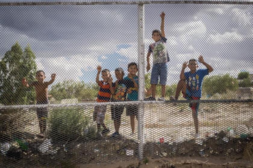Fotografía que muestra un grupo de niños mexicanos que observan la construcción de un muro de acero en la localidad de Sunland Park, en Nuevo México. EFE/Juan Labreche/Archivo