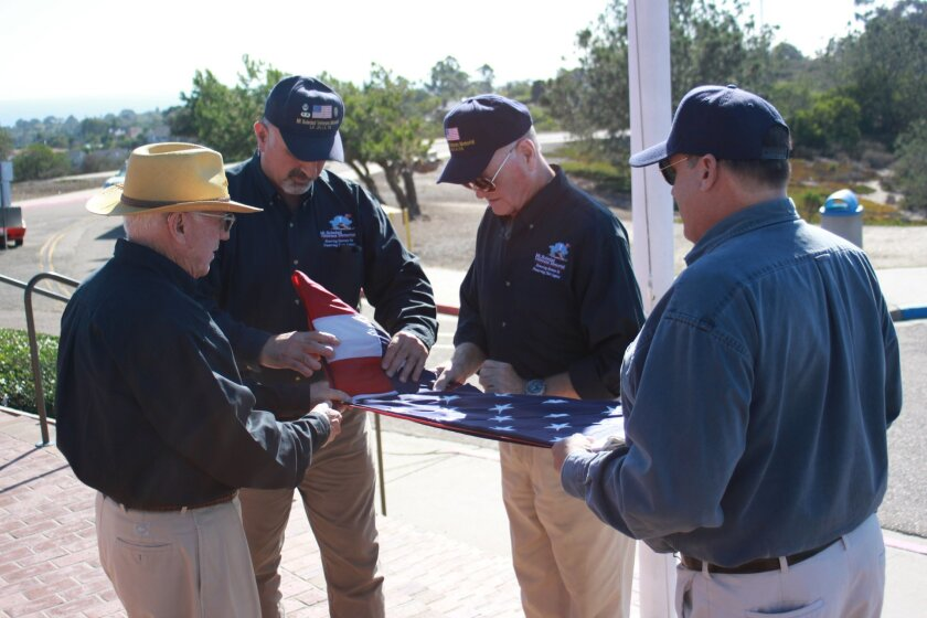 Jim Kitchel, Jim Kyers, Warren Morgan and Rick Preskitt fold the retired flag so a permanent one could go up in its place at the Mount Soledad Veterans Memorial.