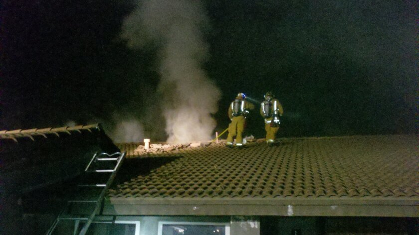 Firefighters battle an attic fire in Escondido Friday night.