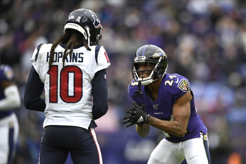 Baltimore Ravens cornerback Marcus Peters (24) claps as Houston Texans wide receiver DeAndre Hopkins (10) lines up against him during the first half of an NFL football game Sunday in Baltimore.