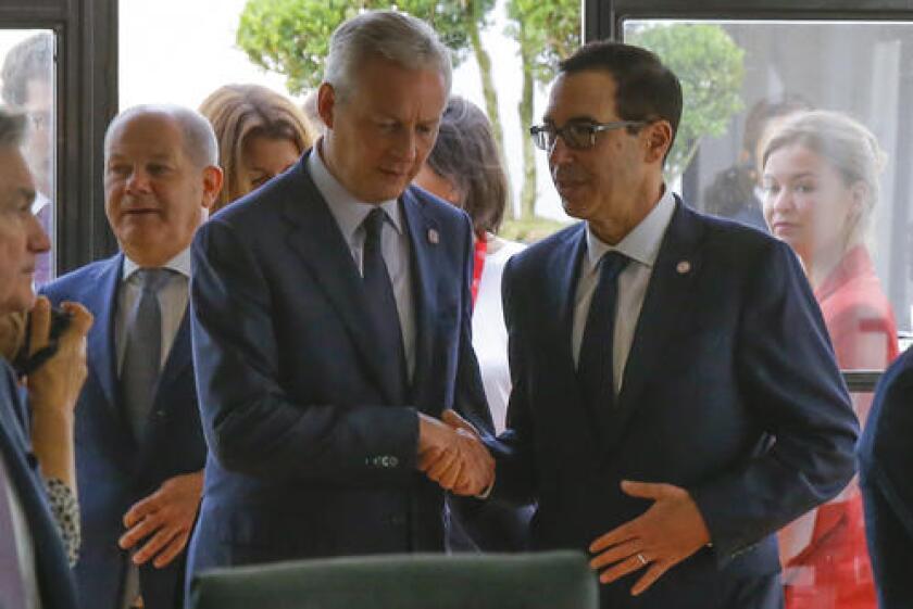 El ministro francés de Finanzas, Bruno Le Maire, a la izquierda, estrecha la mano con el secretario del Tesoro de Estados Unidos, Steve Mnuchin, junto al ministro alemán de Finanzas, Olaf Scholz, al fondo a la izquierda, durante una reunión de los responsables de finanzas del G7 en Chantilly, al norte de París, el jueves 18 de julio de 2019. (AP Foto/Michel Euler)