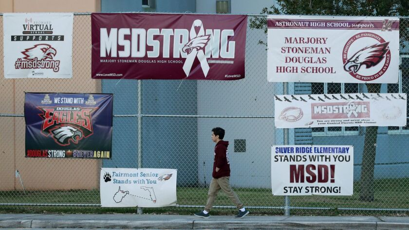 A student walks past signs outside Marjory Stoneman Douglas High School during the one-year annivers