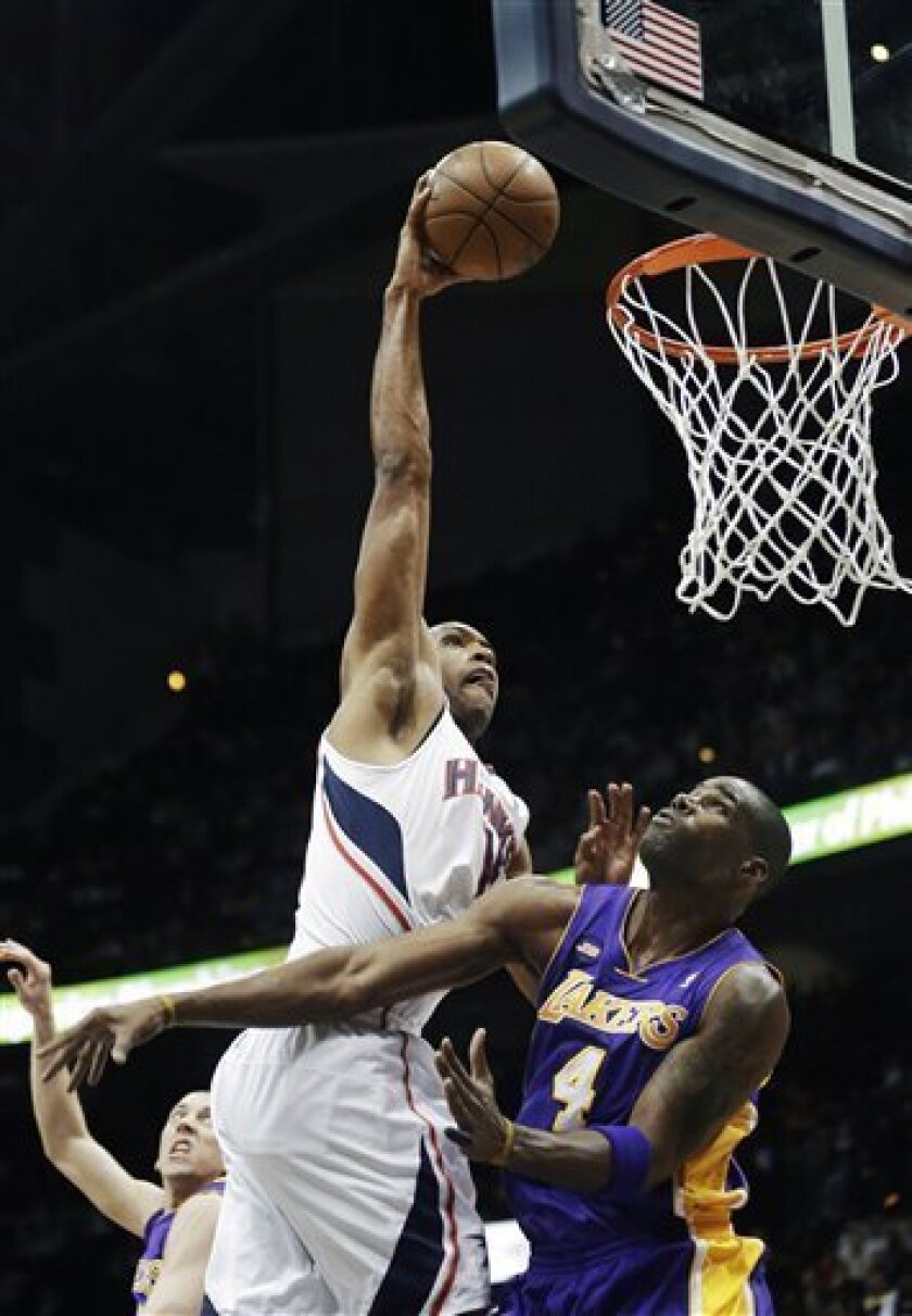 Atlanta Hawks center Al Horford (15) scores against Los Angeles Lakers forward Antawn Jamison (4) in the first half of an NBA basketball game in Atlanta on Wednesday, March 13, 2013. (AP Photo/John Bazemore)