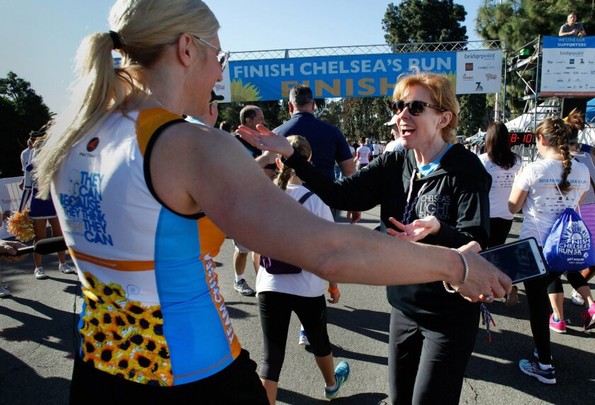 Kelly King, Chelsea King's mother, welcomes runners crossing the finish line at fifth annual Finish Chelsea's Run charity fundraiser in Balboa Park on Saturday.