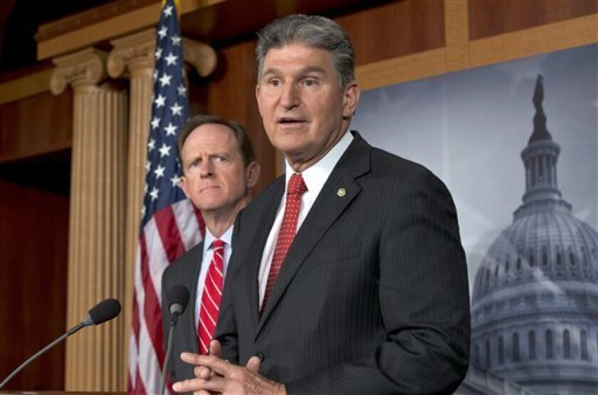 FILE - In this April 10, 2013 file photo, Sen. Joe Manchin, D-W.Va., right, accompanied by Sen. Patrick Toomey, R-Pa., announce that they have reached a bipartisan deal on expanding background checks to more gun buyers,, on Capitol Hill in Washington. The number of Republican senators who might back expanded background checks is now dwindling, threatening a bipartisan effort to subject more gun buyers to the checks. A vote on the compromise, the heart of Congress' gun control effort, is expected