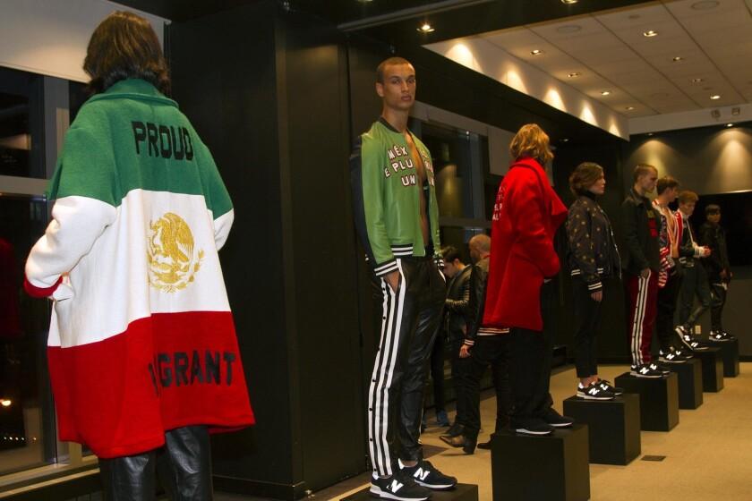 Varios modelos lucen creaciones de la colección Juntos/Together del diseñador mexicano Ricardo Seca, inspirada en los últimos acontecimientos políticos de tensas relaciones entre México y Estados Unidos