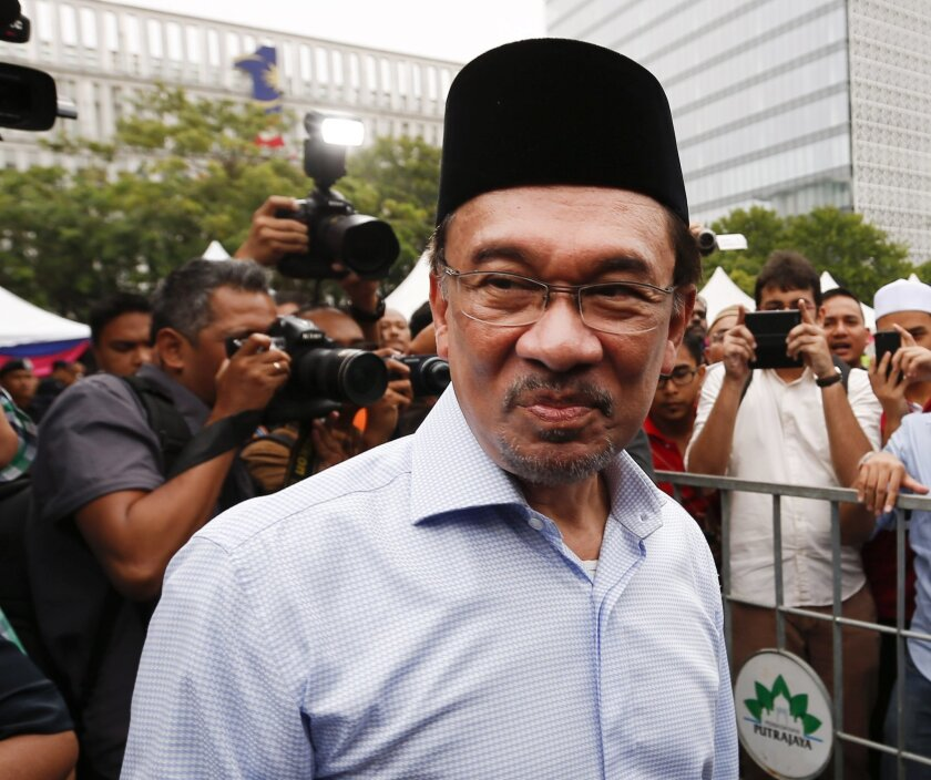 """FILE - In this Nov. 7, 2014 file photo, Malaysian opposition leader Anwar Ibrahim is greeted by his supporters as he returns from a Friday prayer to a court house during the final hearing of his sodomy conviction in Putrajaya, Malaysia. The family of jailed Malaysian opposition leader Anwar has sought a royal pardon in a last-ditch effort to try free him from a sodomy conviction. Nurul Nuha Anwar, his second daughter, said in a statement late Tuesday, Feb. 24, 2015 that there has been a """"miscarriage of justice"""" against her father, whom she described as a """"political prisoner"""". (AP Photo/Vincent Thian, File)"""