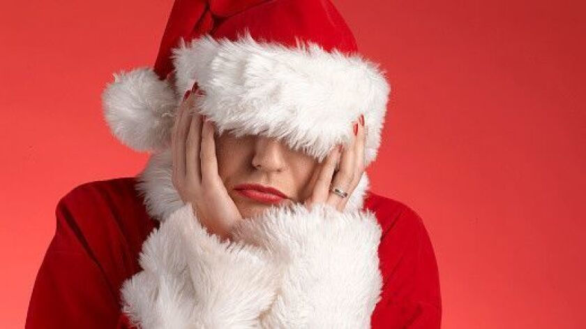 Mrs Claus, Mother / Father Christmas feeling depressed during festivities with head in hands, suffer